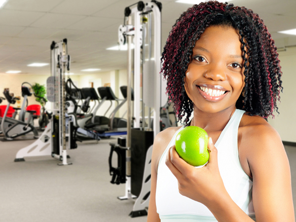 holding apple in exercise room - How to Fuel Your Workout