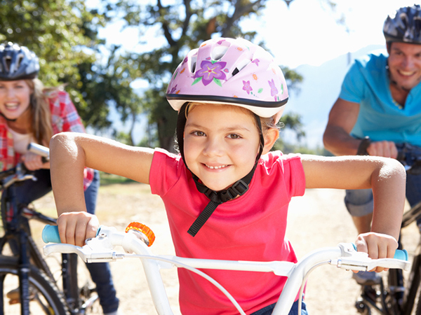 Girl riding bikes with her parents - 19 Easy Ways to Encourage Your Kids to Get Active