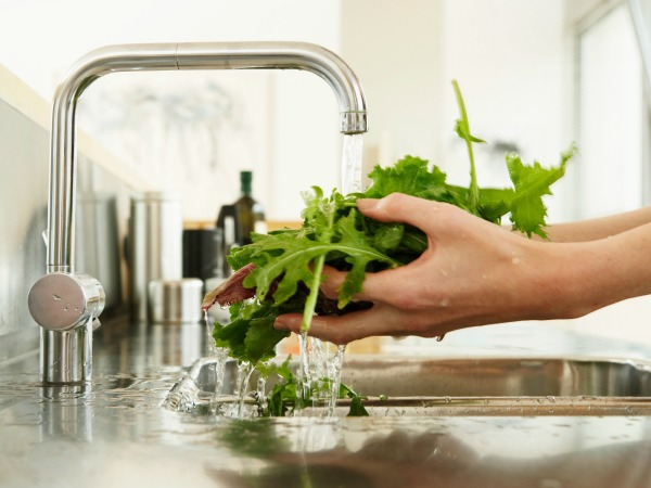 woman washing lettuce at kitchen sink