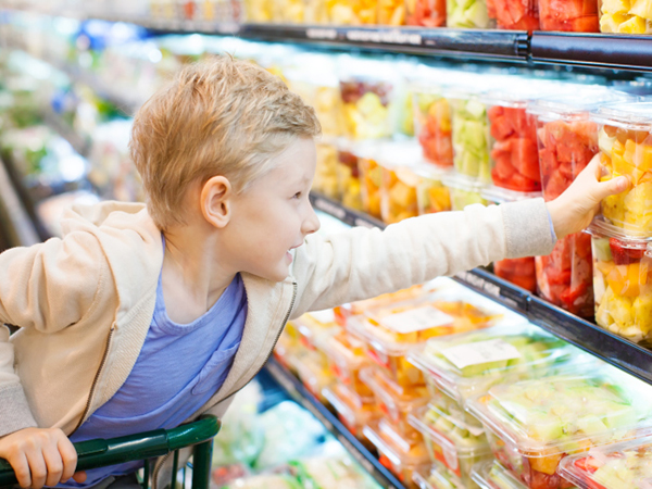 Boy reaching for fruit - Looking to Reduce Your Family's Added Sugar Intake? Here's How