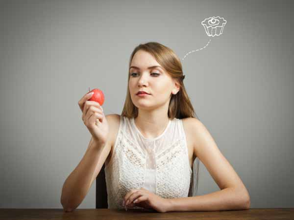 girl looking at apple and thinking about cupcake - Want to Eat Smarter? 3 All-Purpose Tips for Healthier Eating