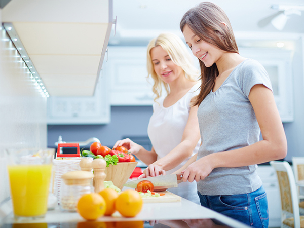 Teen girl and mom cooking - Feeding Your Teen Vegetarian