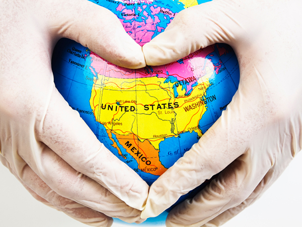 heart shaped hands over globe - 10 Ways RDNs Can Improve the Health of Americans