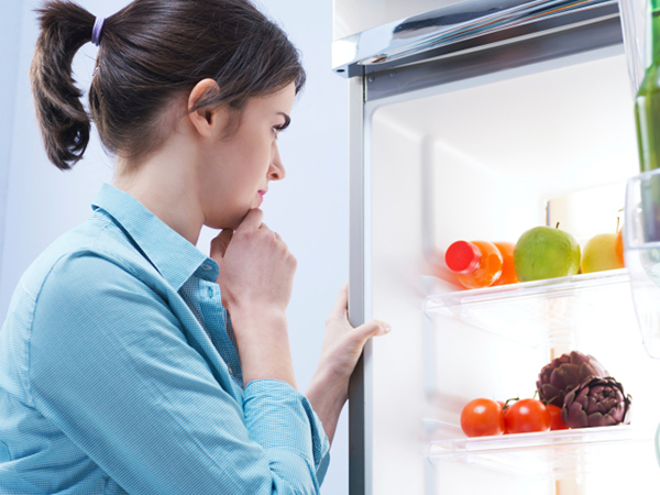 Woman with open refrigerator - What Is the Low FODMAP Diet?