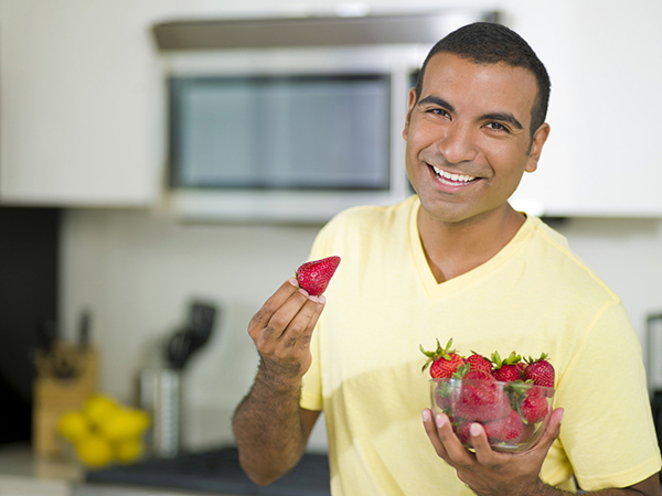 man eating strawberries