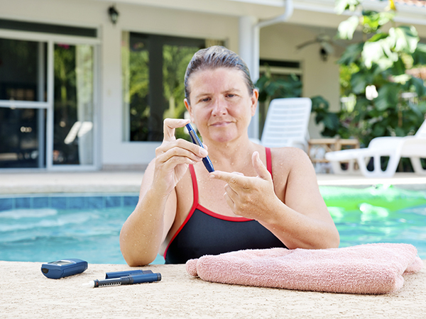 woman in pool with diabetes needle