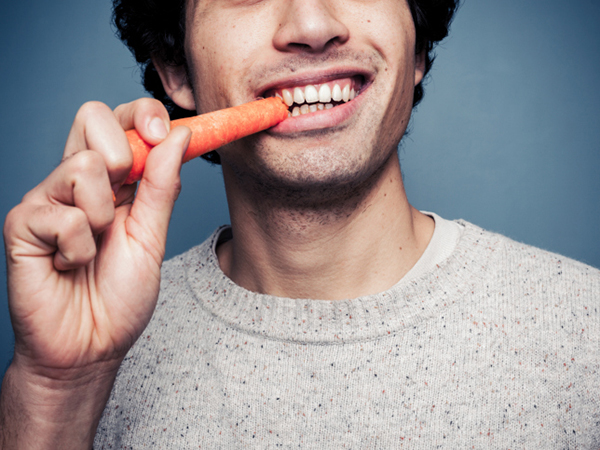 Man eating carrot - Eating Disorders: Problem also Affects Boys and Men
