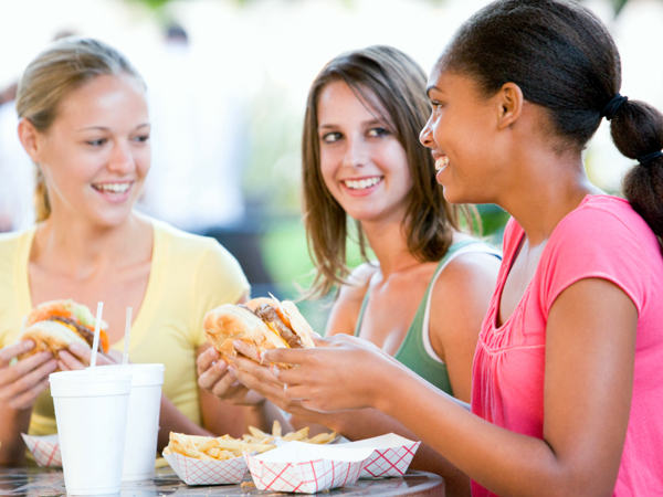 three women eating fast food