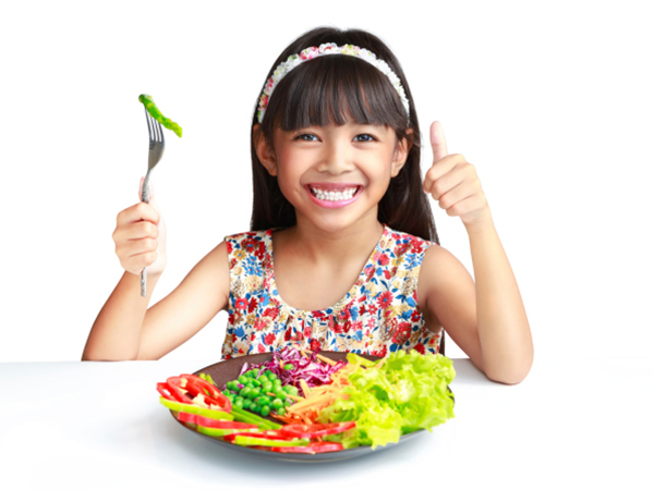 Kid with a plate of vegetables
