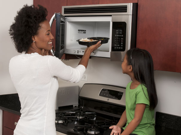 mom and daughter microwaving food