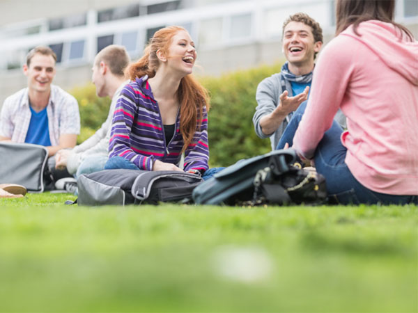 college students sitting on grass
