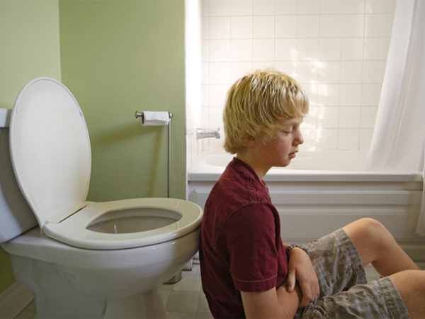 sick kid in front of toilet