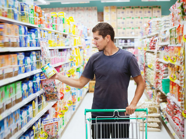 man checking labels at grocery store