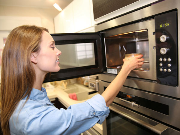 woman putting food in microwave