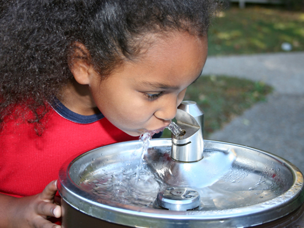Girl at a drinking fountain - Water: How Much Do Kids Need?