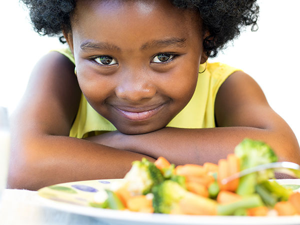 Child with plate of vegetables