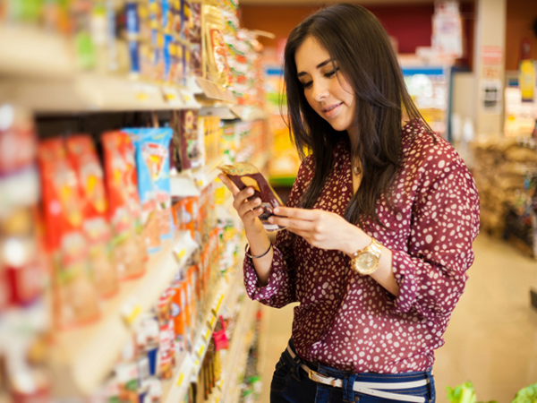 Teenager reading Nutrition Facts on a food label - Teach Your Teen about Nutrition Facts Panels