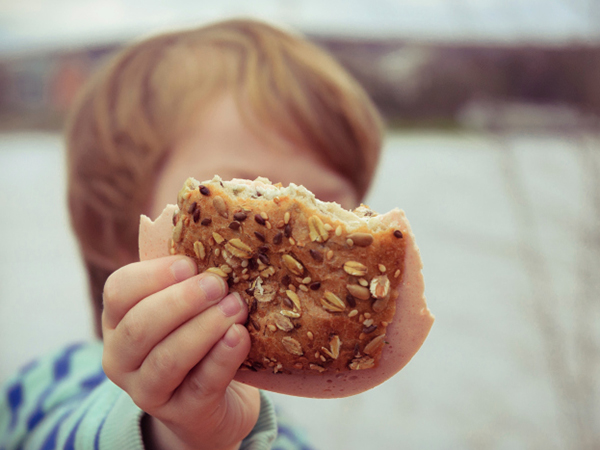 Child holding a sandwich roll - Is a Low-Carb Diet Safe for Kids?