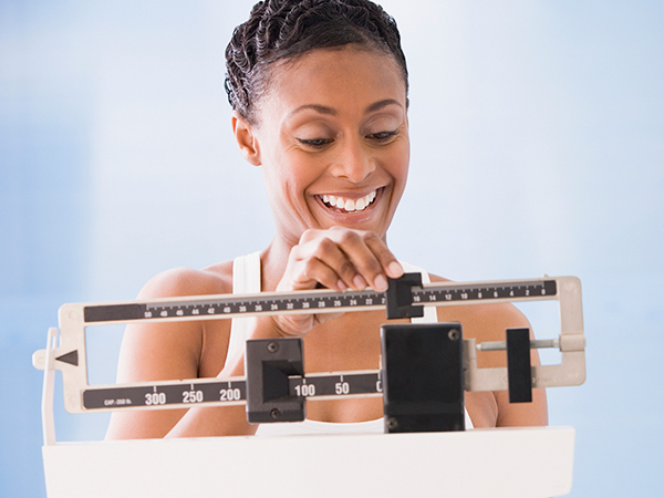 Woman weighing herself - What a Healthy Weight Loss Plan Really Looks Like