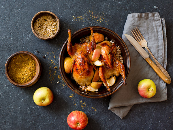 Two cooked quail in pot with apples